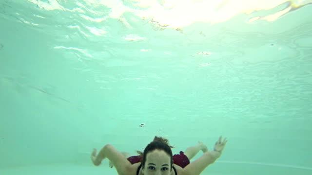 Habillé fille nage dans la piscine