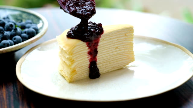slomo - dressing crepe cake with blueberry sauce and fresh blueberry on top - pancake stock videos & royalty-free footage