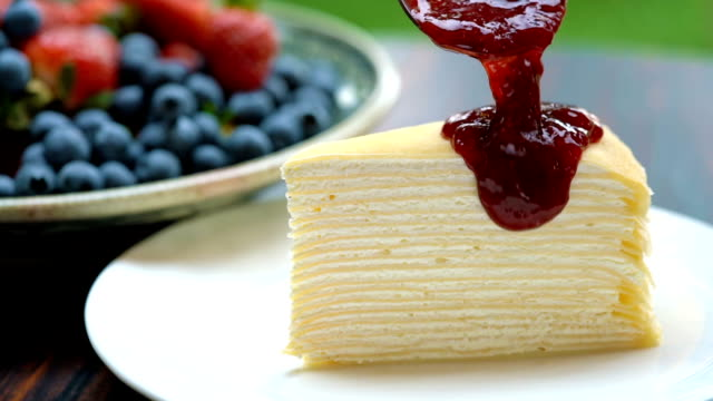slomo - dressing crepe cake with strawberry sauce - syrup stock videos & royalty-free footage