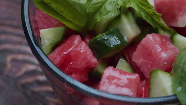 新鮮なサラダにスイカ、ほうれん草、キュウリ、バジルをドレッシング - サラダドレッシング点の映像素材/bロール