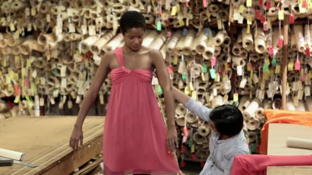 Dressmaker adjusting dress on model