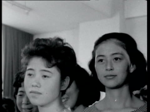 dressmaking class with students watching teacher / students pinning up western style dresses on other students / women drawing designs / students... - 1964年点の映像素材/bロール