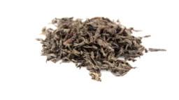 Dried black tea leaves rotate on a plate. Close-up of a rotation of large leaf black tea on a white background. A handful of large leaf black tea rotates on a white plate.