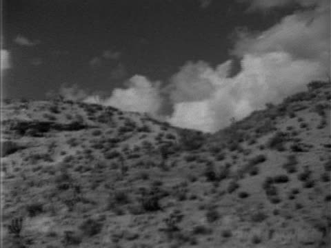 dried grass landscape on mountain low clouds over reverse pan foothills desert scrub to paved road w/ convertible car passing - 1952 stock videos and b-roll footage