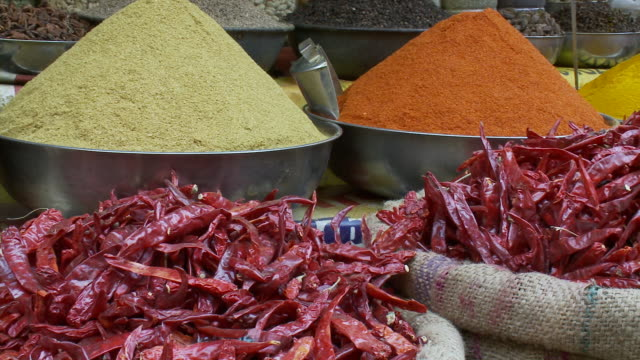 stockvideo's en b-roll-footage met dried red chili peppers and powdered spices are displayed at an outdoor market. - specerij