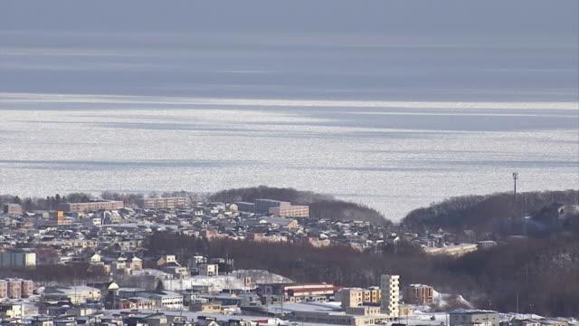 drift ice beyond town, hokkaido, japan - north stock videos & royalty-free footage