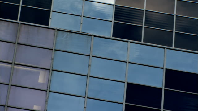 Drifting clouds reflect in the windows of a skyscraper. Available in HD.