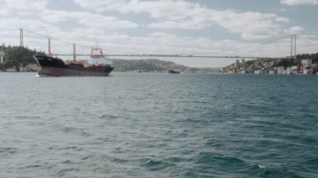 pov drifting through rippling, blue waters passing a ship before approaching the bosporus bridge / turkey - vagare senza meta video stock e b–roll