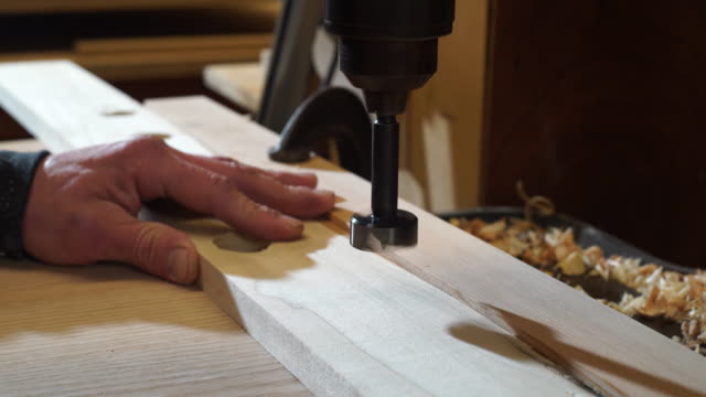 ECU of drill bit cutting through wood on power drill press as wood shavings fly