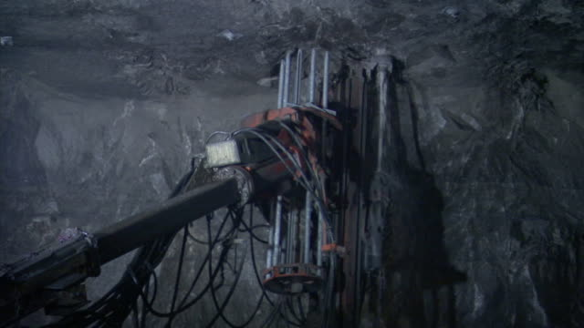 a drill bit extends into the ceiling of a cave. - mining stock videos & royalty-free footage