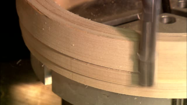 a drill bit shaves wood off a banjo frame. - drill bit stock videos and b-roll footage