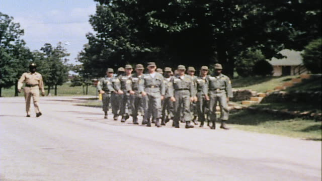 vídeos de stock, filmes e b-roll de ws drill sergeant marching alongside company of recruits in formation / fort leonard wood missouri united states - campo de treinamento militar
