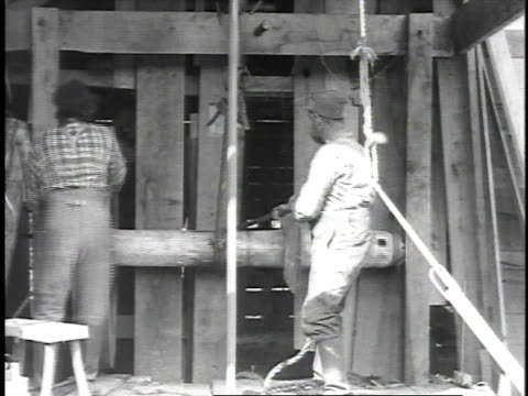 vídeos de stock, filmes e b-roll de 1923 reenactment drillers operating early well digging machine / titusville, pennsylvania, united states - 1923