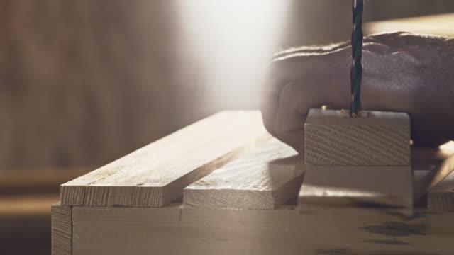 Foratura buco in un pezzo di legno, primo piano
