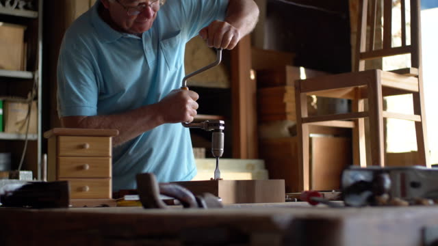 drilling holes in a wooden block - mature men stock videos & royalty-free footage