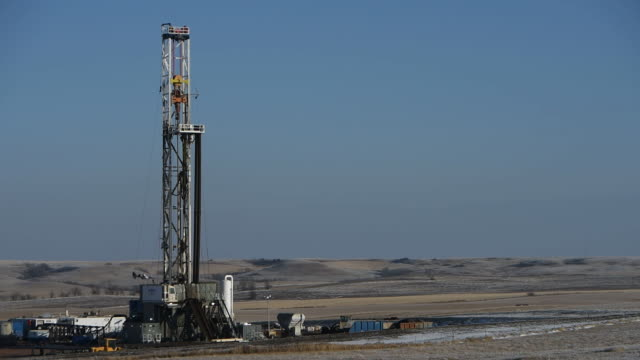 Drilling rigs in Bakken North Dakota US on February 12 Wide shots and close ups of drilling rigs in the middle of a field Wide shots and close ups of...