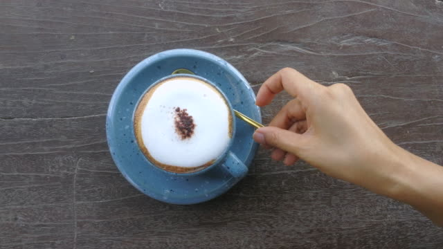 vídeos y material grabado en eventos de stock de beber café de blue cup shot en el teléfono inteligente - table top view