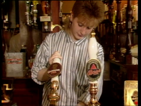 itn lib green man ms people at bar of pub cms woman draws pump as pours beer cms man drinks from pint glass pan down as places empty glass on table... - empty beer glass stock videos and b-roll footage
