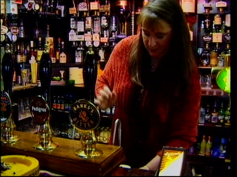 drink-drive limit to be lowered; oxfordshire: woman pulling pint in pub and placing it on bar: bv drinkers at bar. - oxfordshire stock videos & royalty-free footage