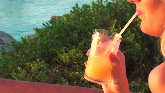drinking a cocktail in the sunset lights - tropical cocktail stock videos & royalty-free footage