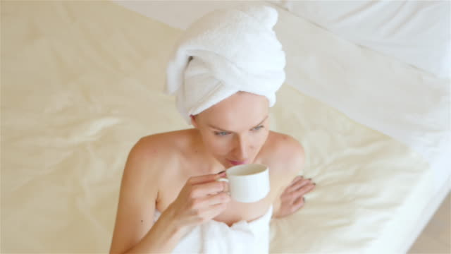 drinking a cup of hot tea in bed - wrapped in a towel stock videos & royalty-free footage