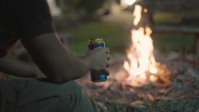 たき火でビールを飲む - 外乗点の映像素材/bロール