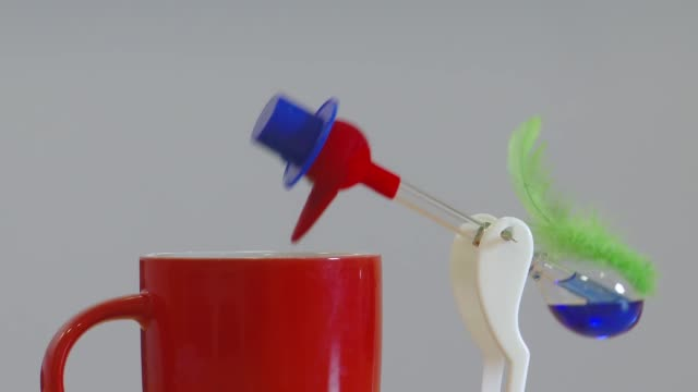 drinking bird dips in and out of mug - 永久運動点の映像素材/bロール