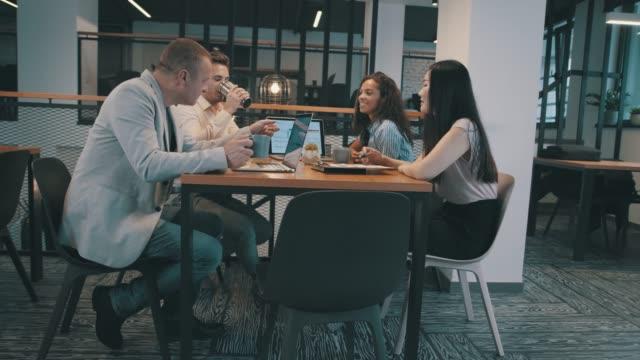 dricka kaffe och diskutera idéer på ett affärsmöte - medarbetarengagemang bildbanksvideor och videomaterial från bakom kulisserna