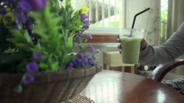 drinking green tea in coffee shop dolly shot - milk tea stock videos & royalty-free footage