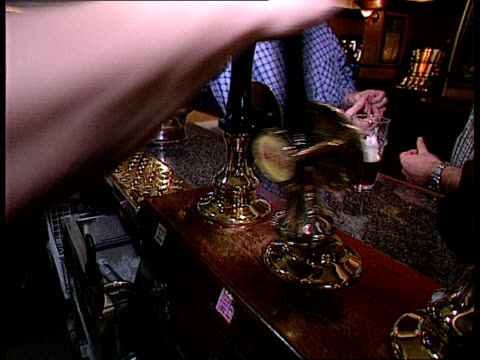 Drinking Guide LIB London Barman in pub pulling pint of beer with hand pump Stout into pint glass