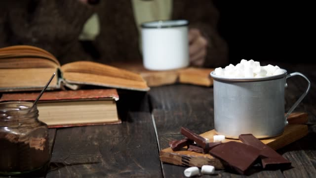 drinking hot chocolate and reading a book - marshmallow video stock e b–roll