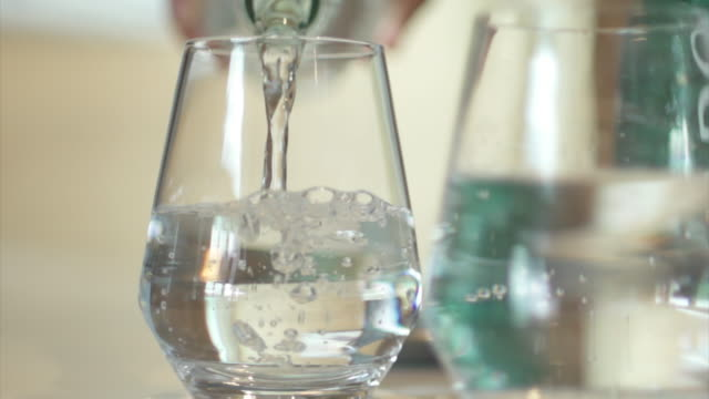 drinking water pouring into a glass. - drinking 個影片檔及 b 捲影像