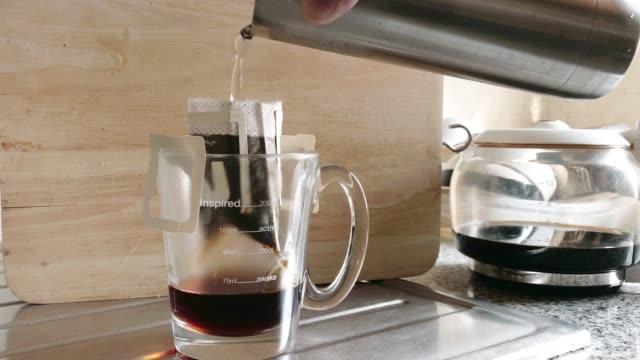 ドリップコーヒーは、木製の背景にキッチンでドリップバッグコーヒーにお湯を注ぎます。 - ステンレス点の映像素材/bロール