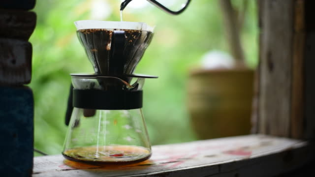 Drip coffee process, The man pouring hot water over the ground on the vintage window.