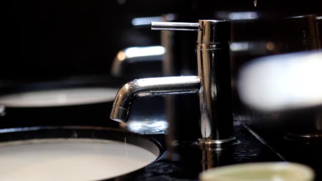 手で蛇口から水が滴る - 空気弁点の映像素材/bロール