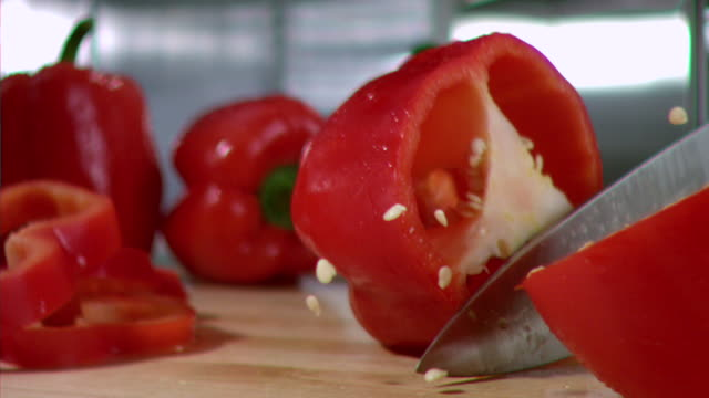 ms pan slo mo dripping wet red pepper being sliced in half by knife / los angeles, ca, united states - peperone video stock e b–roll