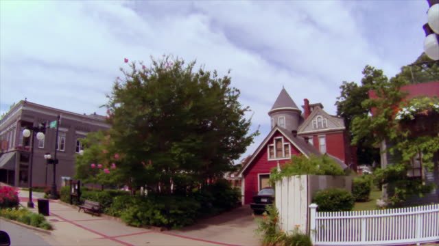 Drive along downtown street featuring quaint old buildings, houses and white picket fence