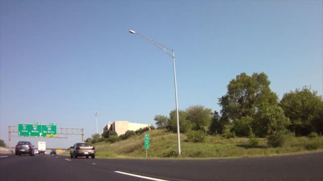 vídeos de stock e filmes b-roll de drive along interstate i-80 with sign, west 70 topeka, north 435, des moines, south 435 wichita - wichita
