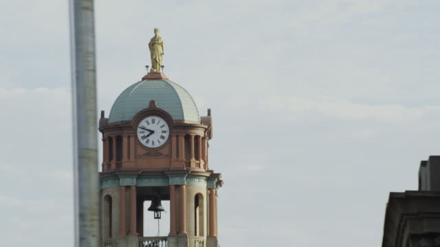 Drive by, close up of the Aberdeen city hall tower featuring a clock - 8:49 - and a golden statue at the top.