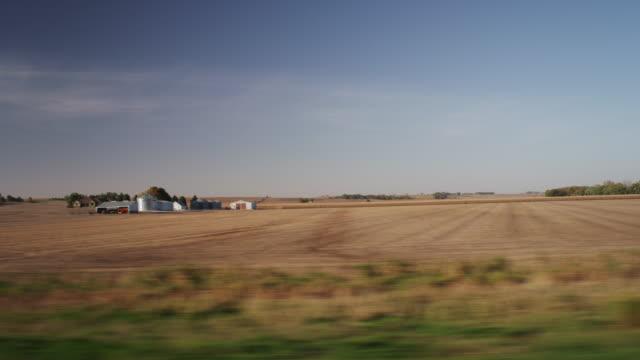 vídeos de stock e filmes b-roll de drive by harvested midwestern farm fields in the distance. - iowa