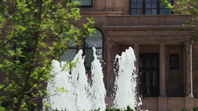 vídeos de stock e filmes b-roll de drive by old stone municipal building with lush garden and water fountain - des moines iowa