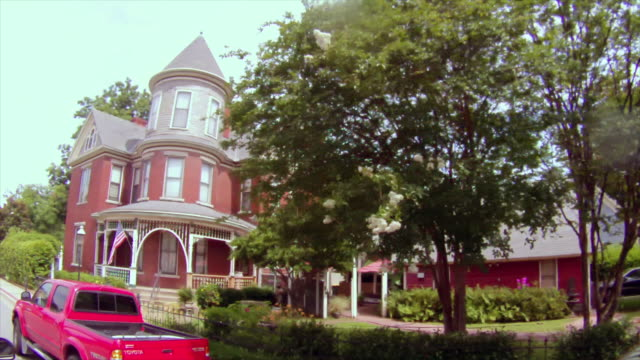 drive by old victorian house with ornate front porch and american flag, wrought iron fence - obsolete stock videos & royalty-free footage