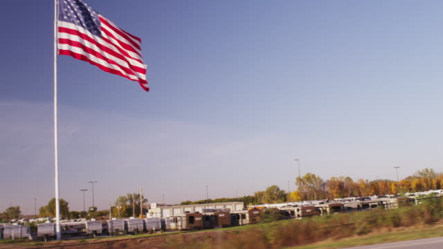 Drive by on the interstate featuring a huge United States flag flying over a parking lot of recreational vehicles.
