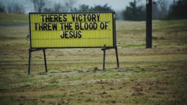 """drive by roadside marquee sign in the old south which reads """"theres victory threw the blood of jesus."""" - roadside stock videos & royalty-free footage"""