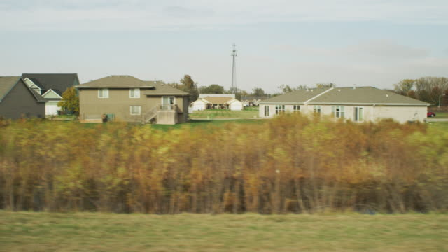 drive by shot through the window of a vehicle passing by a small town low income suburban neighborhood; rear screen projection. - nebraska stock videos & royalty-free footage