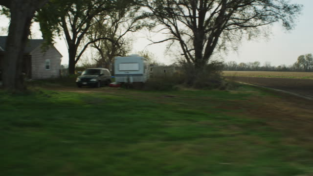 drive by shot through the window of a vehicle traveling down a road next to small farms and desolate fields; rear screen projection. - town stock videos & royalty-free footage