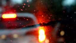 drive car in the city street with rainy day weather, rain drop on windshield with blur light of vehicle on traffic jam urban road