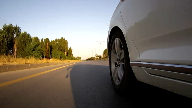 drive on asphalt against sunset with action cam. viewing car tire on the road. - white stock videos & royalty-free footage