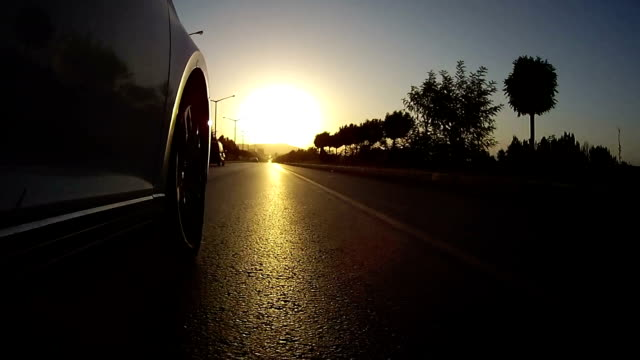 drive on asphalt against sunset with action cam. viewing car tire on the road. - inquadratura dal basso video stock e b–roll