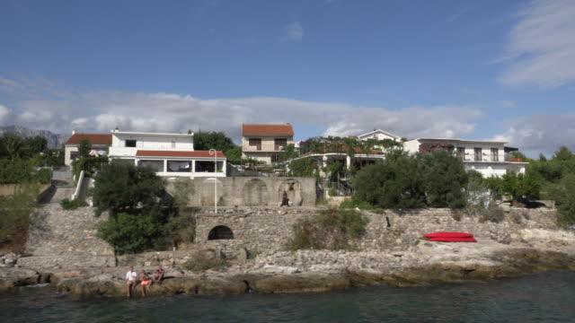 POV / Drive past a holiday village at rocky coast